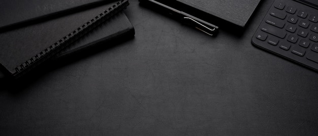 Espaço de trabalho escuro de luxo com livros de agenda, caneta, tablet digital com espaço de teclado e cópia