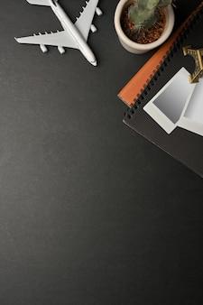 Espaço de trabalho escuro e criativo com layout plano, com moldura de cartão fotográfico, itens de viagem e simulação de cena