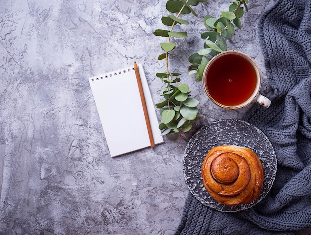 Espaço de trabalho feminino com bun, xícara de chá e notebook