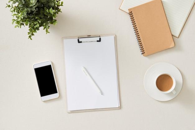 Espaço de trabalho feminino com caderno de papel, caneta, acessórios em branco. mesa de escritório feminina plana