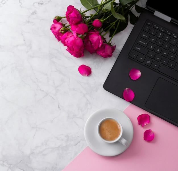 Espaço de trabalho feminino com computador portátil, buquê de rosas e café em uma mesa de mármore.