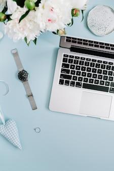 Espaço de trabalho feminino com laptop, buquê de flores de peônia branca, acessórios em azul