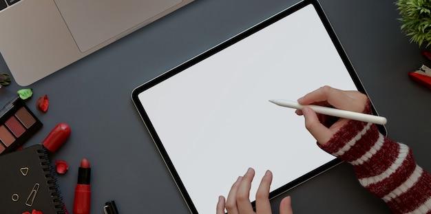 Espaço de trabalho feminino com o conceito de luxo vermelho, vista superior da mulher que trabalha com tablet