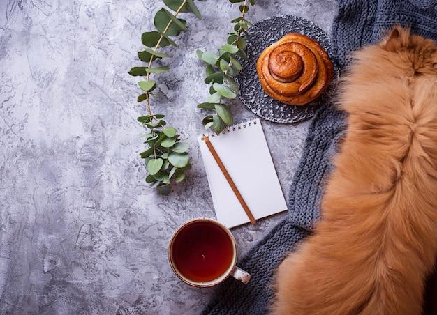Espaço de trabalho feminino com pão, xícara de chá, caderno e gato