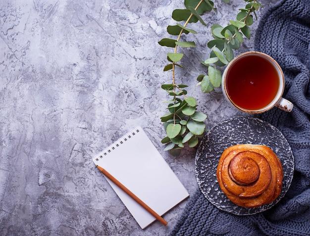 Espaço de trabalho feminino com pão, xícara de chá e notebook. vista plana leiga