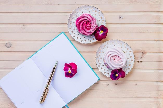 Espaço de trabalho feminino com papel em branco, flor rosa, lápis. conceito de negócios. configuração plana, vista superior. bom dia, planejamento. marshmallow e um livro aberto. momentos românticos.