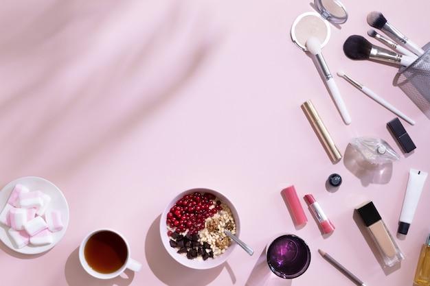 Espaço de trabalho feminino com xícara de café, flocos de aveia, maquiagem e conjunto de cosméticos, na mesa rosa pastel com sombra, vista superior e plana leigos. moda rosa mulher local de trabalho para os blogs. café da manhã linda.
