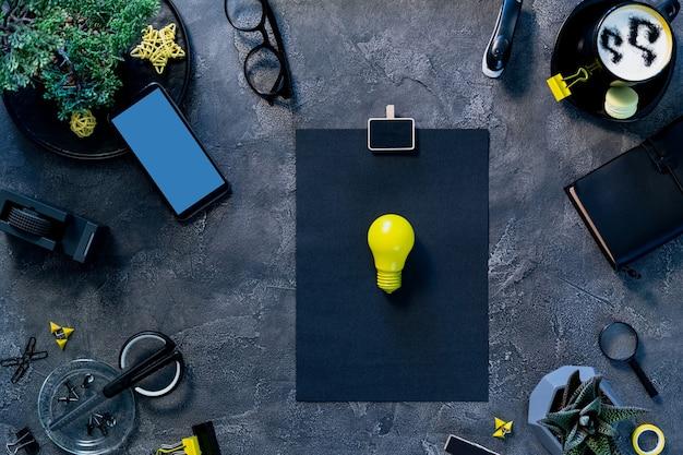 Espaço de trabalho freelancer elegante. mesa de mesa de escritório em casa plana lay. lâmpada de ideia amarela na página de papel, tela em branco do smartphone e vista superior estacionária.