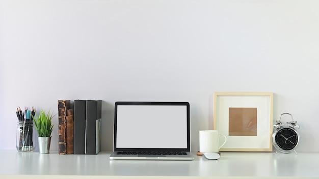 Espaço de trabalho laptop contemporânea tela vazia, livros, lápis, café e foto moldura com despertador.