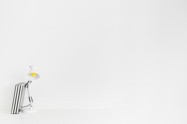 Espaço de trabalho minimalista com lâmpada e livros