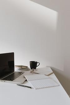 Espaço de trabalho minimalista da mesa do escritório em casa. laptop na mesa com xícara de café, folha de papel, artigos de papelaria contra uma parede branca