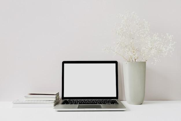Espaço de trabalho minimalista em uma mesa de escritório em casa com laptop, buquê de flores rosa