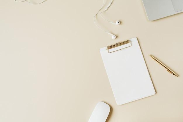 Espaço de trabalho minimalista na mesa do escritório em casa com área de transferência, laptop, fones de ouvido em bege
