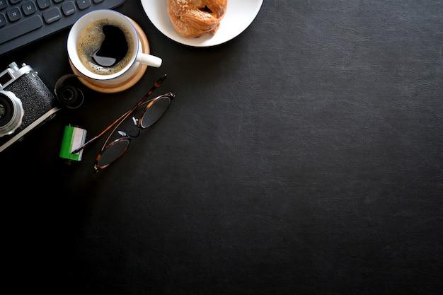 Espaço de trabalho mínimo com computador, câmera vintage em fundo de couro escuro