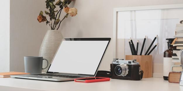 Espaço de trabalho mínimo com computador laptop, câmera, material de escritório e vaso de rosas secas
