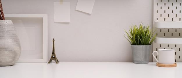 Espaço de trabalho mínimo com espaço de cópia, decorações, bloco de notas e prateleira na mesa branca