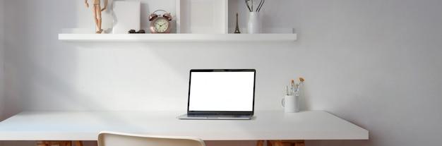 Espaço de trabalho mínimo com laptop de tela em branco e copie o espaço com decorações na prateleira branca