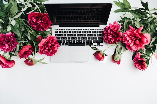 Espaço de trabalho mínimo com laptop e flores de peônia rosa em fundo branco. camada plana, vista superior