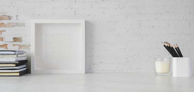 Espaço de trabalho mínimo com moldura e material de escritório na mesa branca com cópia espaço e parede de tijolo