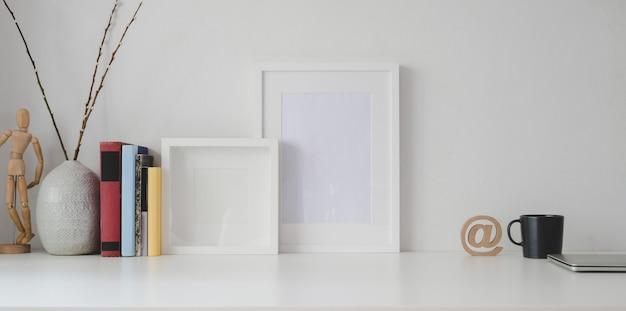 Espaço de trabalho mínimo com moldura em branco e material de escritório, mesa de madeira branca