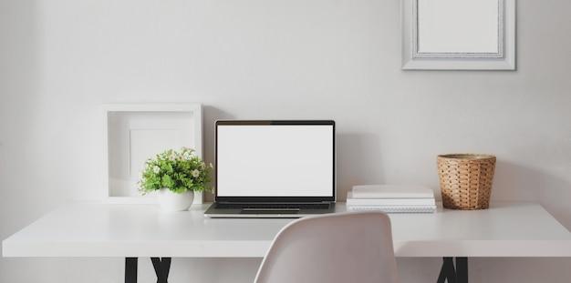 Espaço de trabalho mínimo com o computador portátil de tela em branco aberta com mock up frame