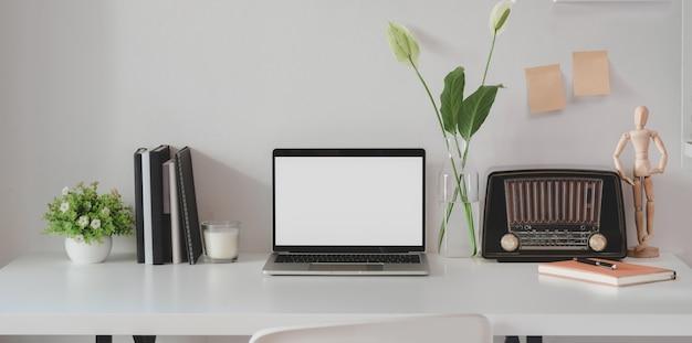 Espaço de trabalho mínimo com o computador portátil de tela em branco aberta com rádio vintage