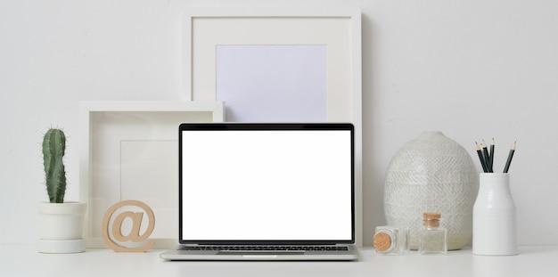 Espaço de trabalho mínimo com o laptop de tela aberta em branco com quadros de mock-up e decoração de vaso de cerâmica