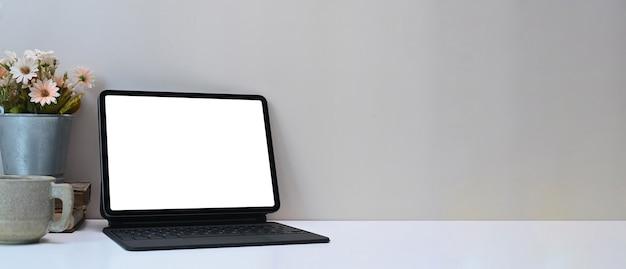 Espaço de trabalho mínimo com tablet de computador monitor de tela em branco branca, planta, xícara de café e espaço de cópia na mesa branca.
