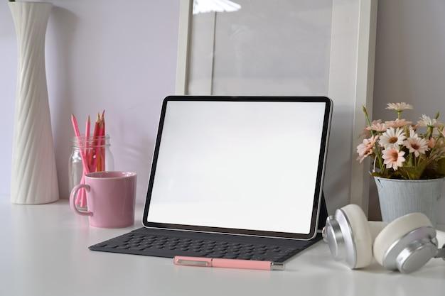 Espaço de trabalho mínimo com tablet de tela em branco.