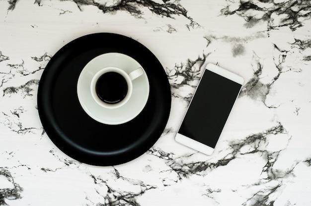 Espaço de trabalho mínimo com xícara de café, smartphone em mármore elegante