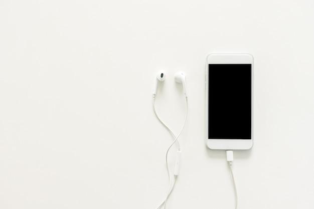 Espaço de trabalho mínimo - creative flat lay foto da mesa do espaço de trabalho com fones de ouvido e telefone celular com tela em branco no espaço da cópia fundo branco. topo da vista, fotografia de lay lay up.