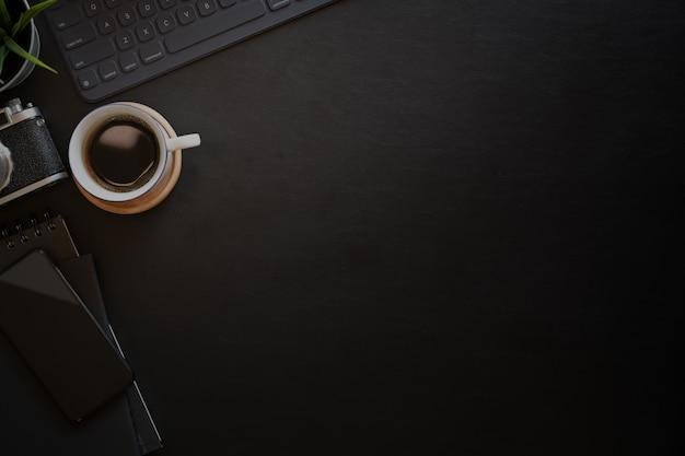 Espaço de trabalho mínimo do fotógrafo da mesa de couro escura, tiro da vista superior