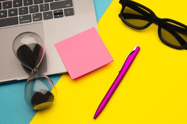 Espaço de trabalho mínimo - foto criativa plana de mesa de trabalho com teclado de laptop, caneta e ampulheta