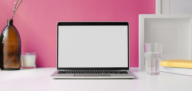 Espaço de trabalho moderno com computador portátil de tela em branco aberto com mock up frame e material de escritório na mesa branca e parede rosa