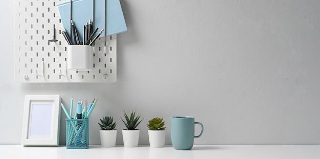 Espaço de trabalho moderno com moldura branca, papelaria, xícara de café e planta de casa em uma mesa bem organizada.