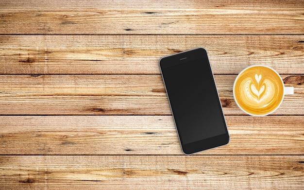 Espaço de trabalho moderno com xícara de café e tablet ou smartphone na madeira