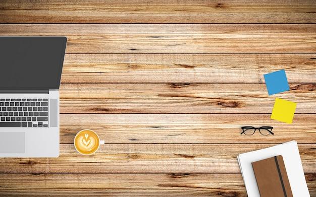 Espaço de trabalho moderno com xícara de café, papel, caderno, tablet ou smartphone e laptop na madeira