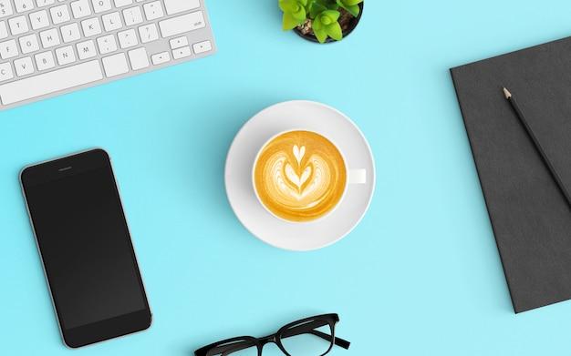 Espaço de trabalho moderno com xícara de café, smartphone, teclado e notebook na cor azul