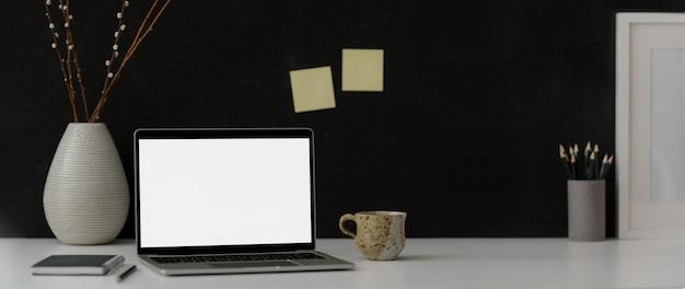 Espaço de trabalho moderno escuro com laptop, artigos de papelaria, decorações e espaço de cópia
