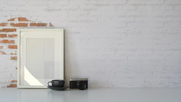 Espaço de trabalho moderno, quadro de cartaz em branco e parede de tijolo vazio