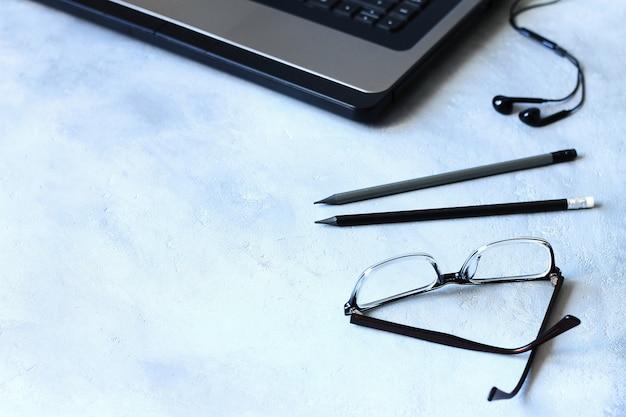 Espaço de trabalho, muitos itens diferentes, incluindo um laptop, óculos, notebook e fones de ouvido estão na mesa.