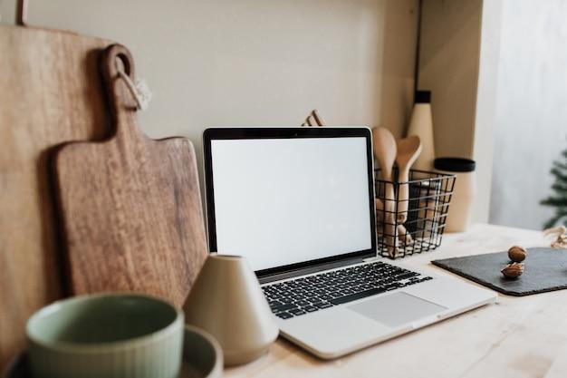 Espaço de trabalho na cozinha com laptop e utensílios de cozinha