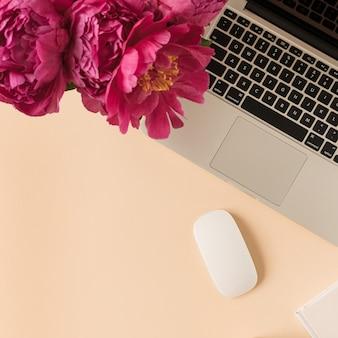 Espaço de trabalho na mesa do escritório doméstico com laptop, buquê de flores de peônia rosa em superfície de pêssego