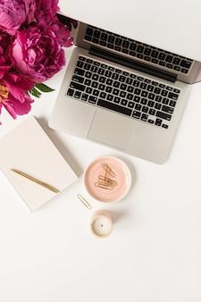 Espaço de trabalho na mesa do escritório doméstico com laptop, buquê de flores de peônia rosa