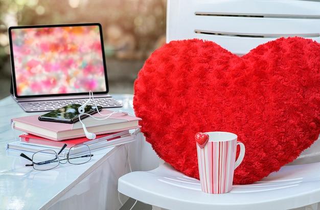 Espaço de trabalho no conceito de dia dos namorados com caneca rosa e almofada vermelha na cadeira.