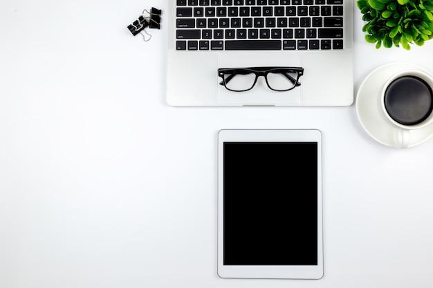 Espaço de trabalho no escritório com tablet e com telas vazias em branco estão no topo