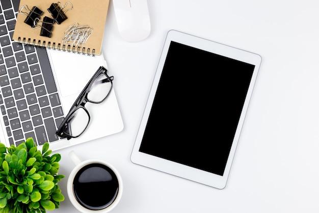 Espaço de trabalho no escritório com tablet e com telas vazias em branco.