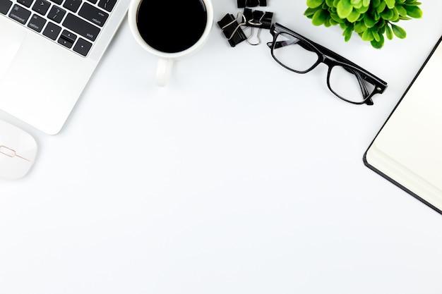 Espaço de trabalho no escritório, mesa branca com caderno em branco e outros materiais de escritório