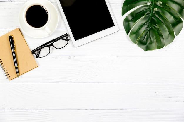 Espaço de trabalho no escritório, mesa de madeira branca com caderno em branco e outros materiais de escritório