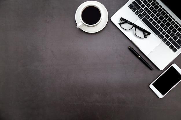Espaço de trabalho no escritório, mesa preta com caderno em branco e outros materiais de escritório.